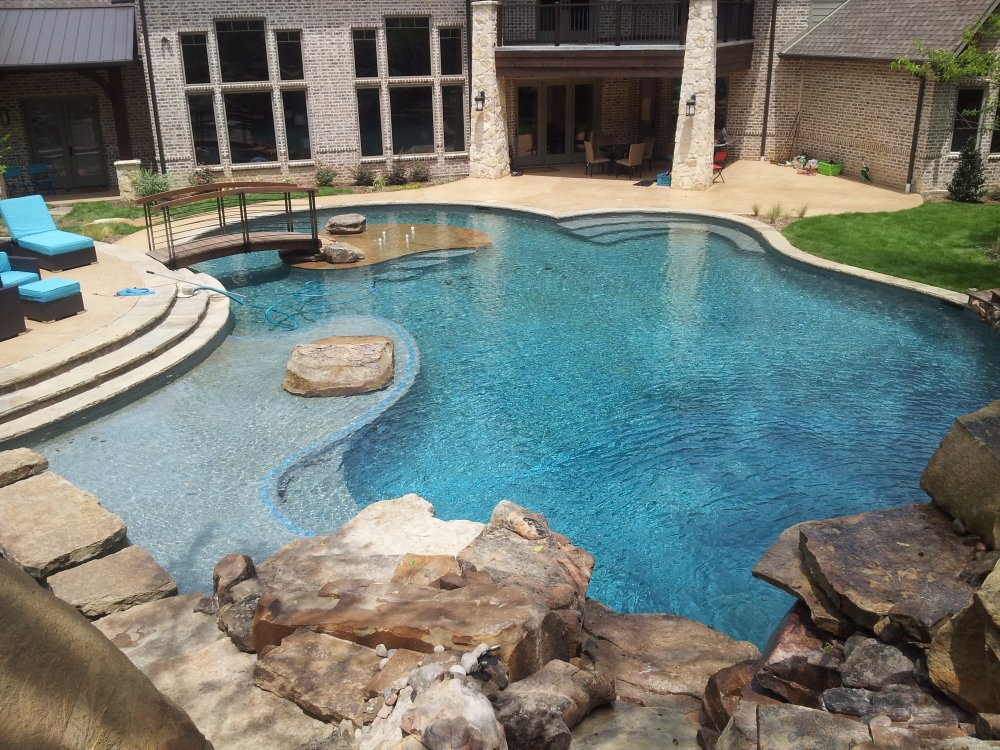 tanning_deck_waterfall_swimming_pool_island_boulder